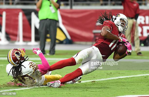 Wide receiver Larry Fitzgerald of the Arizona Cardinals is hit in the end zone by cornerback EJ Biggers of the Washington Redskins during the second...