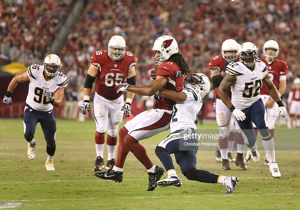 Wide receiver Larry Fitzgerald #11 of the Arizona Cardinals is tackled after a reception during the preseason NFL game against the San Diego Chargers at the University of Phoenix Stadium on August 24, 2013 in Glendale, Arizona.
