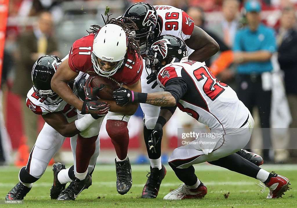 Wide receiver <a gi-track='captionPersonalityLinkClicked' href=/galleries/search?phrase=Larry+Fitzgerald&family=editorial&specificpeople=183380 ng-click='$event.stopPropagation()'>Larry Fitzgerald</a> #11 of the Arizona Cardinals is tackled by cornerback <a gi-track='captionPersonalityLinkClicked' href=/galleries/search?phrase=Desmond+Trufant&family=editorial&specificpeople=6348548 ng-click='$event.stopPropagation()'>Desmond Trufant</a> #21, defensive end <a gi-track='captionPersonalityLinkClicked' href=/galleries/search?phrase=Jonathan+Massaquoi&family=editorial&specificpeople=7234601 ng-click='$event.stopPropagation()'>Jonathan Massaquoi</a> #96 and free safety Thomas DeCoud #28 of the Atlanta Falcons after a reception during the NFL game at the University of Phoenix Stadium on October 27, 2013 in Glendale, Arizona. The Cardinals defeated the Falcons 27-13.