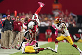 Wide receiver Larry Fitzgerald of the Arizona Cardinals leaps over strong safety Bashaud Breeland of the Washington Redskins after a reception during...