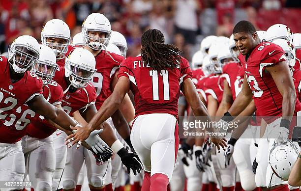 Wide receiver Larry Fitzgerald of the Arizona Cardinals runs out to greet teammates during introductions to the preseason NFL game against the Kansas...