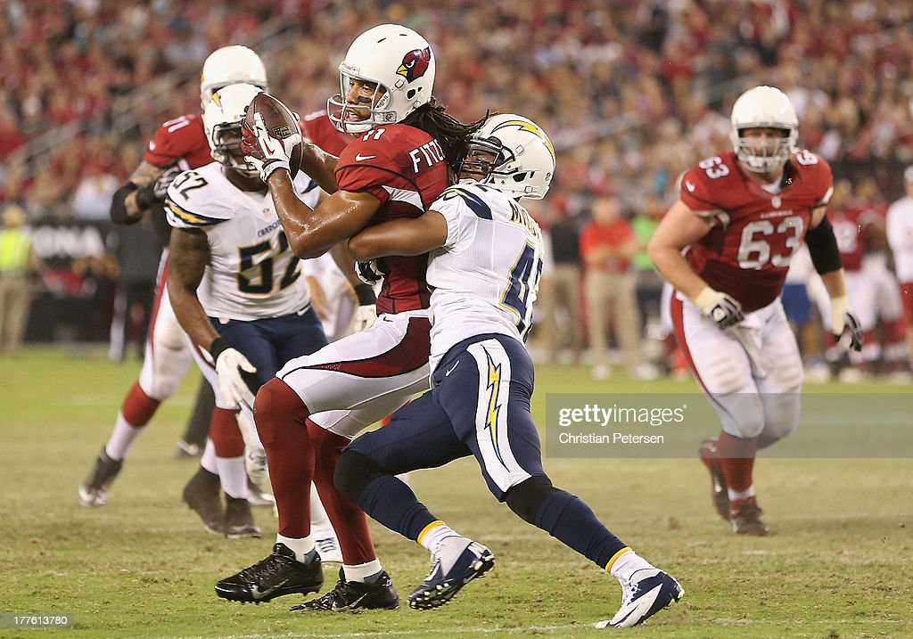 Wide receiver Larry Fitzgerald #11 of the Arizona Cardinals runs with the football after a reception against cornerback William Middleton #42 of the San Diego Chargers during the preseason NFL game at the University of Phoenix Stadium on August 24, 2013 in Glendale, Arizona.