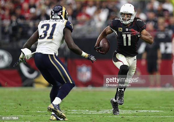 Wide receiver Larry Fitzgerald of the Arizona Cardinals runs with the ball in front of free safety Maurice Alexander of the Los Angeles Rams during...