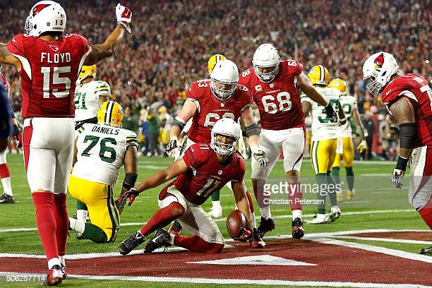 Wide receiver Larry Fitzgerald of the Arizona Cardinals scores a 5 yard touchdown reception against the Green Bay Packers in overtime of the NFC...