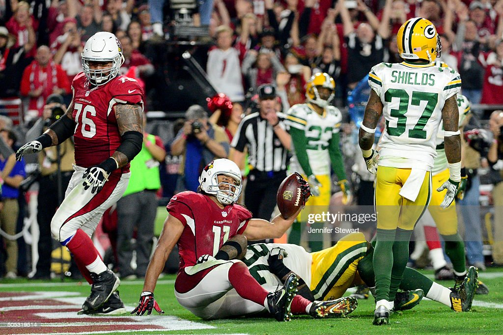 Wide receiver Larry Fitzgerald of the Arizona Cardinals scores the game winning touchdown during overtime of the NFC Divisional Playoff Game at...