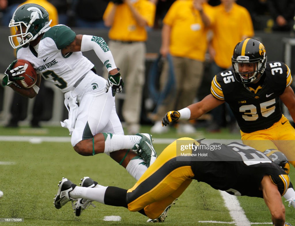 Wide receiver Macgarrett Kings Jr. #3 of the Michigan State Spartans rushes up field during the first quarter past defensive back Gavin Smith #35 and wide receiver Jordan Cotton #23 of the Iowa Hawkeyes on October 5, 2013 at Kinnick Stadium in Iowa City, Iowa. Michigan State won 26-14.