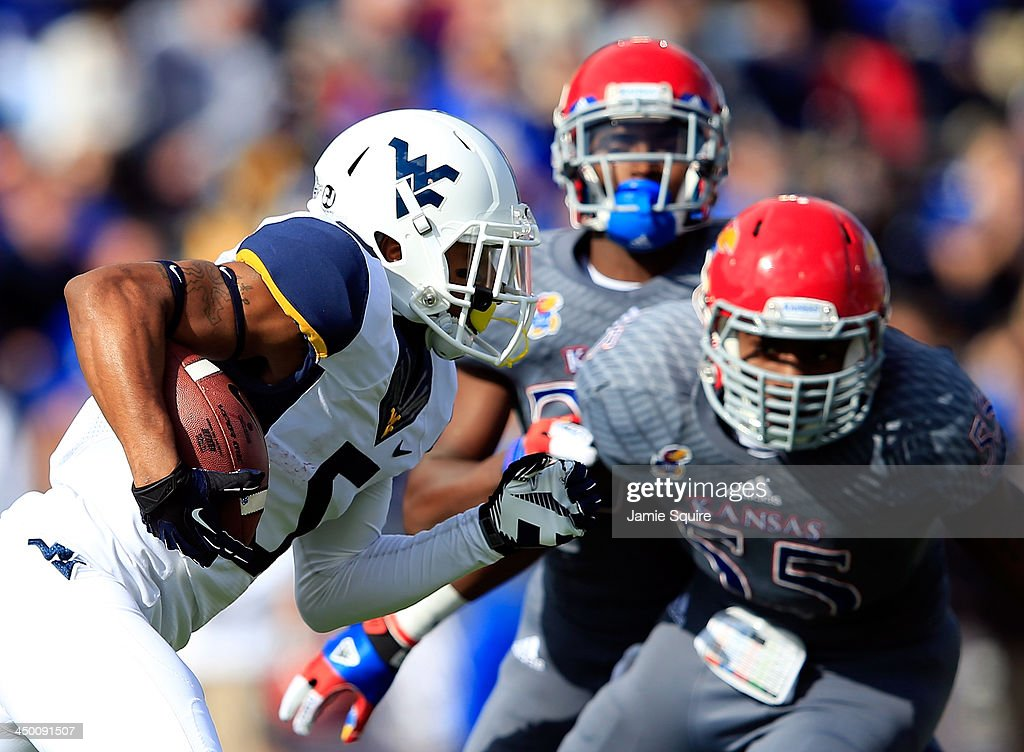 Wide receiver Mario Alford #5 of the West Virginia Mountaineers carries the ball as linebacker Michael Reynolds #55 of the Kansas Jayhawks defends during the game at Memorial Stadium on November 16, 2013 in Lawrence, Kansas.