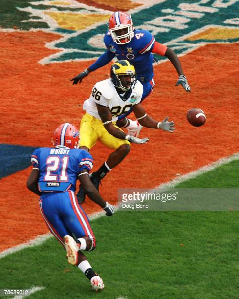 Wide receiver Mario Manningham of the Michigan Wolverines catches a touchdown pass between safety Major Wright and cornerback Wondy PierreLouis of...