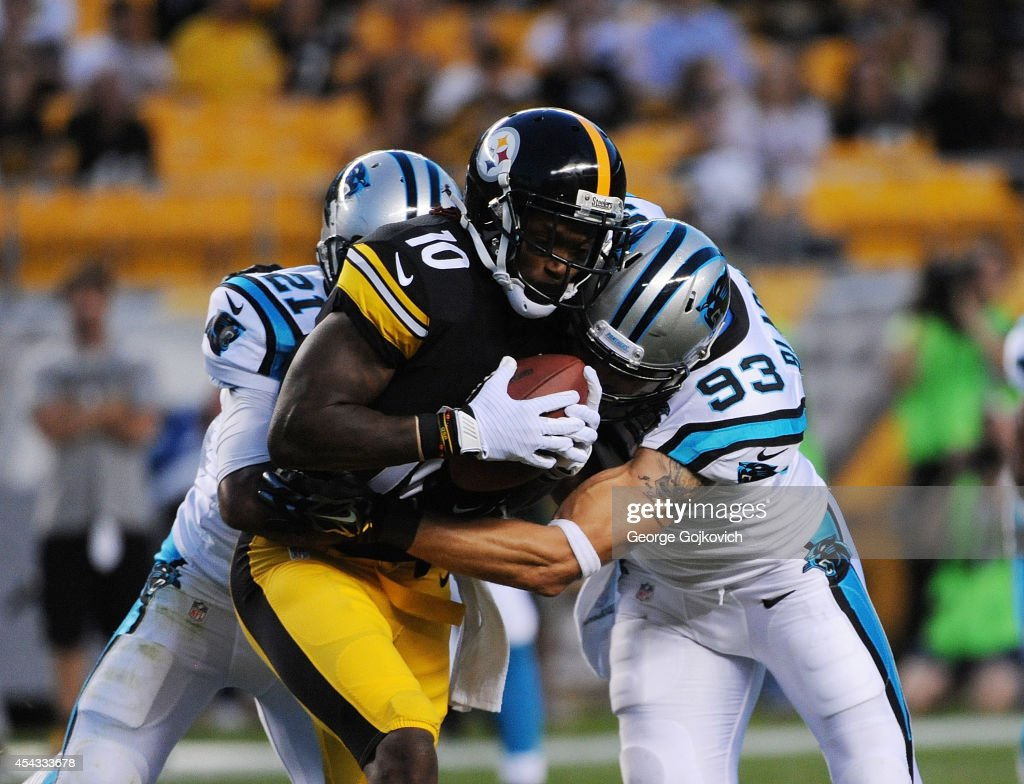 Wide receiver Martavis Bryant of the Pittsburgh Steelers is tackled by safety Thomas DeCoud and linebacker Chase Blackburn of the Carolina Panthers...