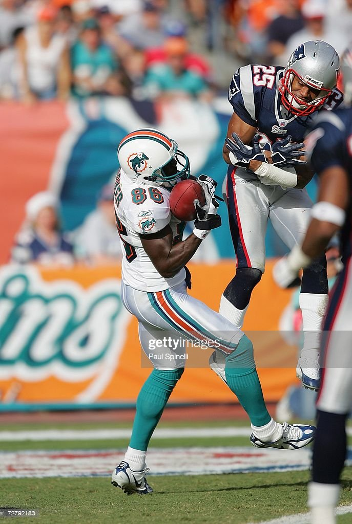 Wide receiver Marty Booker #86 of the Miami Dolphins catches a touchdown pass for a 13-0 lead while covered by safety Artrell Hawkins #25 of the New England Patriots at Dolphin Stadium on December 10, 2006 in Miami, Florida. The Dolphins defeated the Patriots 21-0.