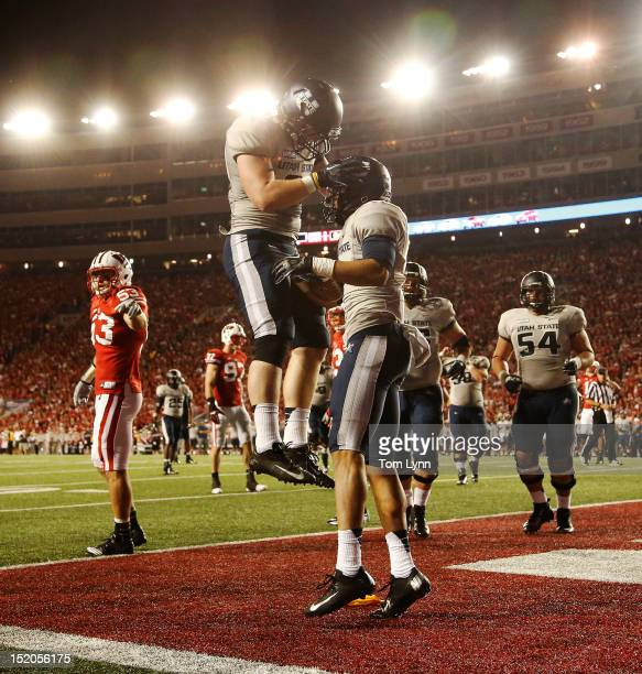 Wide receiver Matt Austin of the Utah State Aggies is met by teammate tight end Kellen Bartlett after scoring a second quarter touchdown against the...