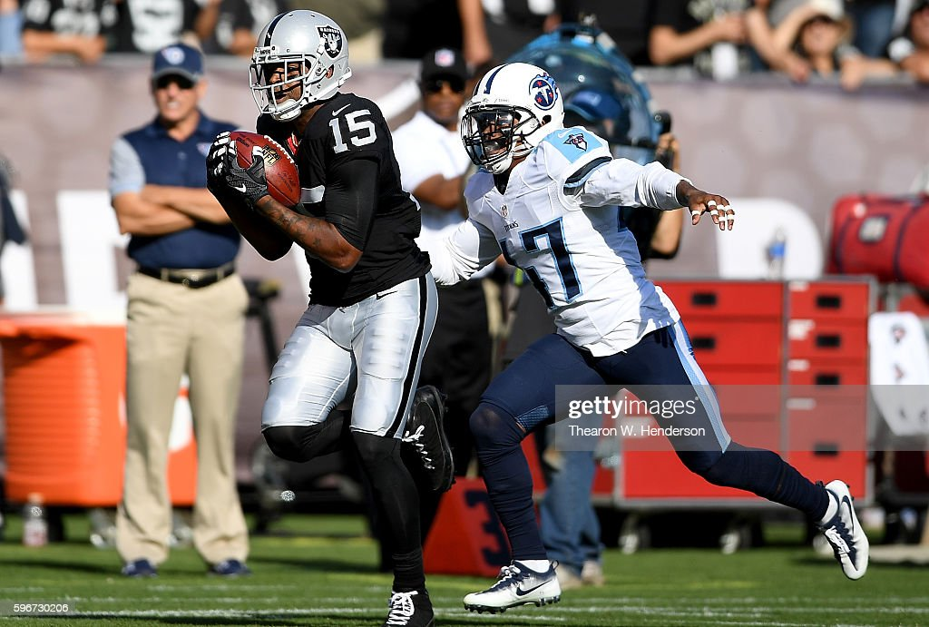 Wide receiver Michael Crabtree #15 of the Oakland Raiders catches a 41 yard pass over defensive back Antwon Blake #47 of the Tennessee Titans in the first half of their preseason football game at the Oakland Coliseum on August 27, 2016 in Oakland, California.