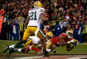 Wide receiver Michael Crabtree of the San Francisco 49ers catches a touchdown pass thrown by quarterback Colin Kaepernick against the Green Bay...
