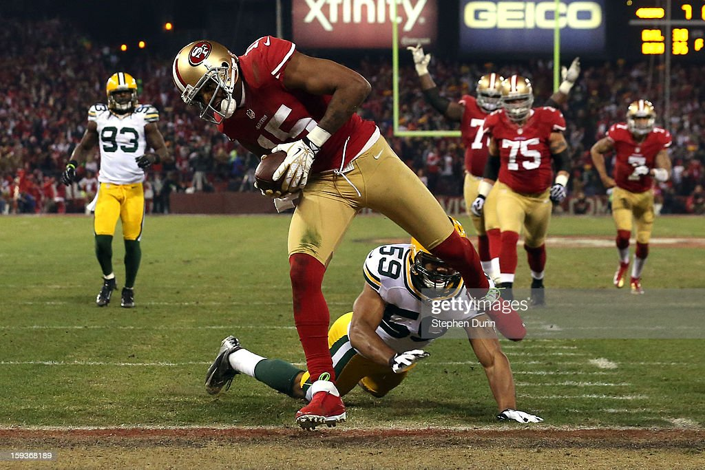 Wide receiver Michael Crabtree #15 of the San Francisco 49ers runs the ball in for a touchdown thrown by quarterback Colin Kaepernick #7 in the second quarter against the Green Bay Packers during the NFC Divisional Playoff Game at Candlestick Park on January 12, 2013 in San Francisco, California.