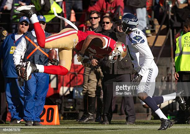 Wide receiver Michael Crabtree of the San Francisco 49ers snags a pass and heads for the ground in front of cornerback Byron Maxwell of the Seattle...