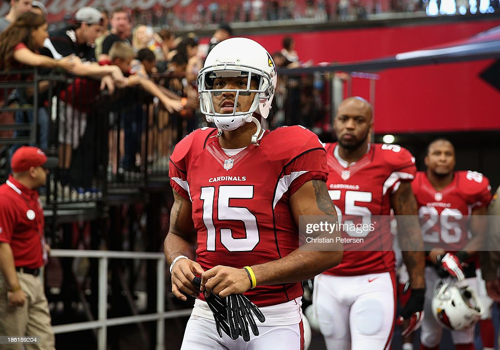 Wide receiver Michael Floyd #15 of the Arizona Cardinals leads John Abraham #55 and <a gi-track='captionPersonalityLinkClicked' href=/galleries/search?phrase=Rashad+Johnson&family=editorial&specificpeople=3941326 ng-click='$event.stopPropagation()'>Rashad Johnson</a> #26 onto the field before the NFL game against the Atlanta Falcons at the University of Phoenix Stadium on October 27, 2013 in Glendale, Arizona. The Cardinals defeated the Falcons 27-13.