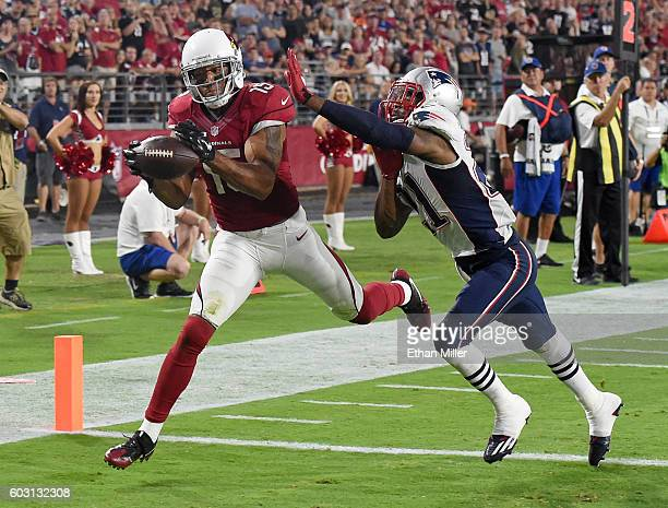 Wide receiver Michael Floyd of the Arizona Cardinals misses a pass in the end zone under pressure from cornerback Malcolm Butler of the New England...