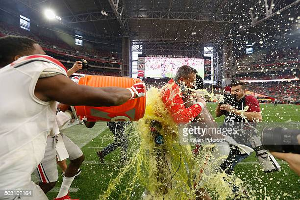 Wide receiver Michael Thomas of the Ohio State Buckeyes and running back Ezekiel Elliott douse head coach Urban Meyer with Gatorade after the fourth...