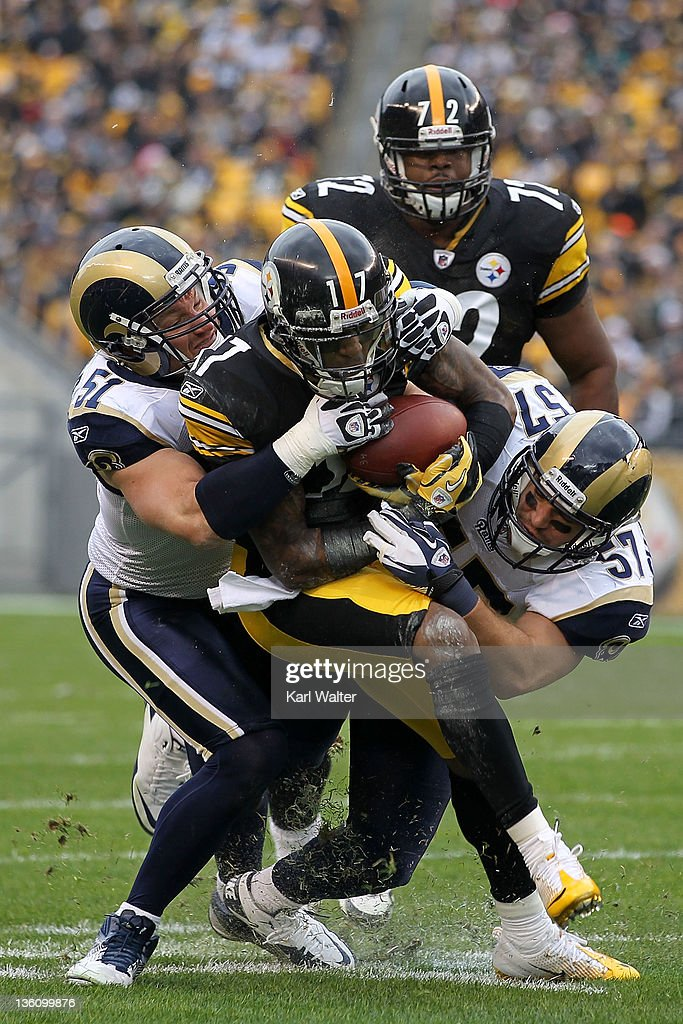 Wide receiver Mike Wallace #17 of the Pittsburgh Steelers is tackled by linebackers Brady Poppinga #51 and Chris Chamberlain #57 of the St. Louis Rams during the game at Heinz Field on December 24, 2011 in Pittsburgh, Pennsylvania.