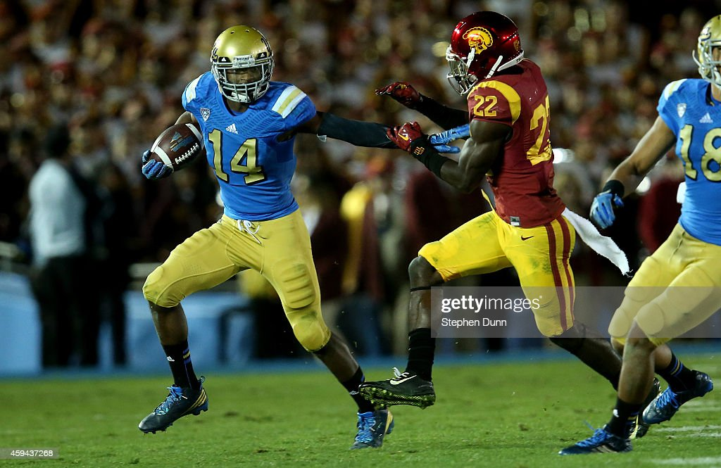 Wide receiver Mossi Johnson #1 of the UCLA Bruins stiff arms defensive back Leon McQuay III #22 of the USC Trojans at the Rose Bowl on November 22, 2014 in Pasadena, California. UCLA on 38-20.