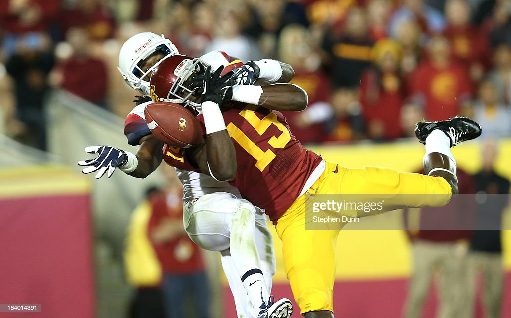 Wide receiver Nelson Agholor #15 of the USC Trojans can't hang onto a pass in the end zone as cornerback Jonathan McKnight #6 of the Arizona Wildcats defends at Los Angeles Coliseum on October 10, 2013 in Los Angeles, California. USC won 38-31.