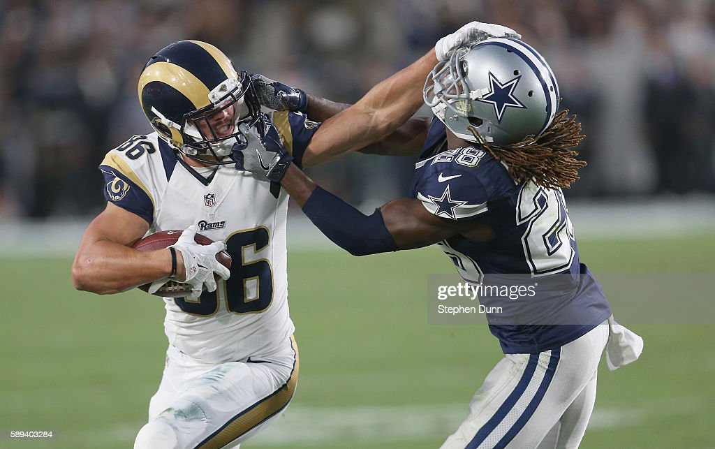 Wide receiver Nelson Spruce of the Los Angeles Rams carries the ball as he battles cornerback Dax Swanson of the Dallas Cowboys at the Los Angeles...