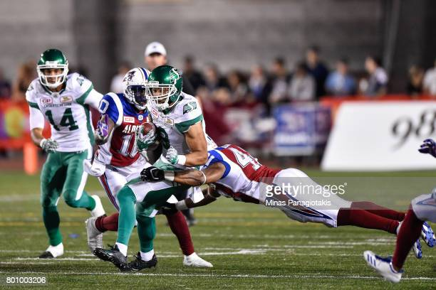 Wide receiver Nic Demski of the Saskatchewan Roughriders protects the ball from fullback JeanSamuel Blanc of the Montreal Alouettes during the CFL...