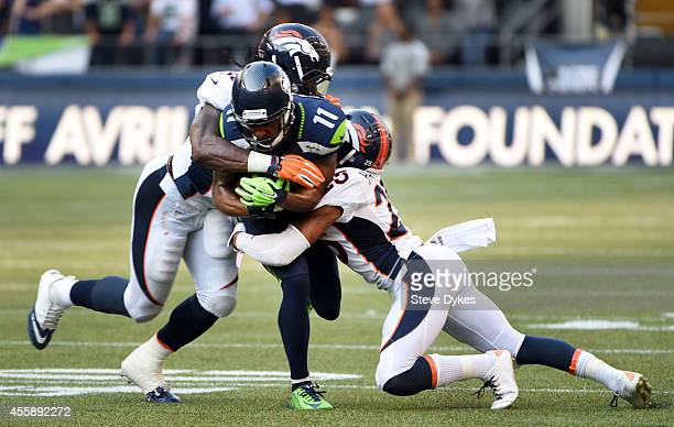 Wide receiver Percy Harvin of the Seattle Seahawks is tackled by middle linebacker Nate Irving and cornerback Chris Harris of the Denver Broncos...