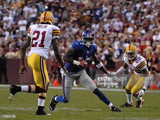Wide receiver Plaxico Burress of the New York Giants looks to elude safety Sean Taylor of the Washington Redskins on his way to a 33 yard touchdown...