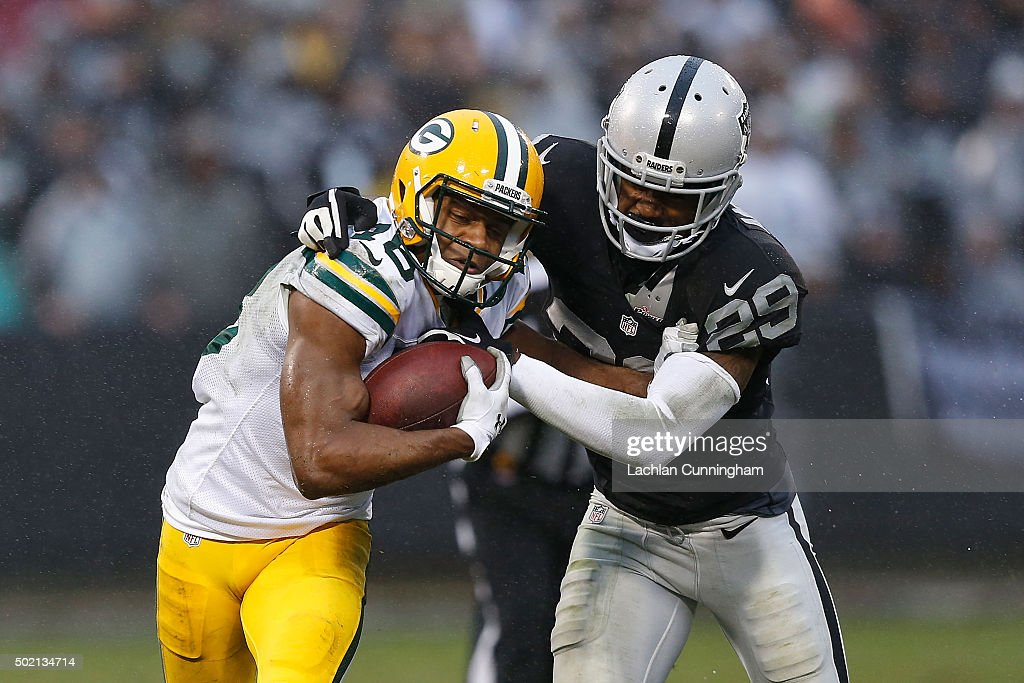 Wide Receiver <a gi-track='captionPersonalityLinkClicked' href=/galleries/search?phrase=Randall+Cobb+-+American+Football+Player&family=editorial&specificpeople=9773987 ng-click='$event.stopPropagation()'>Randall Cobb</a> #18 of the Green Bay Packers is tackled by Corner Back <a gi-track='captionPersonalityLinkClicked' href=/galleries/search?phrase=David+Amerson&family=editorial&specificpeople=7244765 ng-click='$event.stopPropagation()'>David Amerson</a> #29 of the Oakland Raiders at O.co Coliseum on December 20, 2015 in Oakland, California.