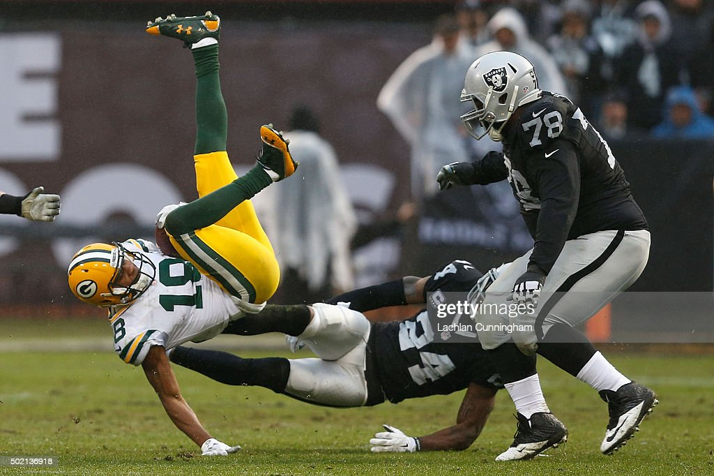 Wide Receiver Randall Cobb #18 of the Green Bay Packers is tackled by Corner Back Charles Woodson #24 of the Oakland Raiders in the second quarter at O.co Coliseum on December 20, 2015 in Oakland, California.