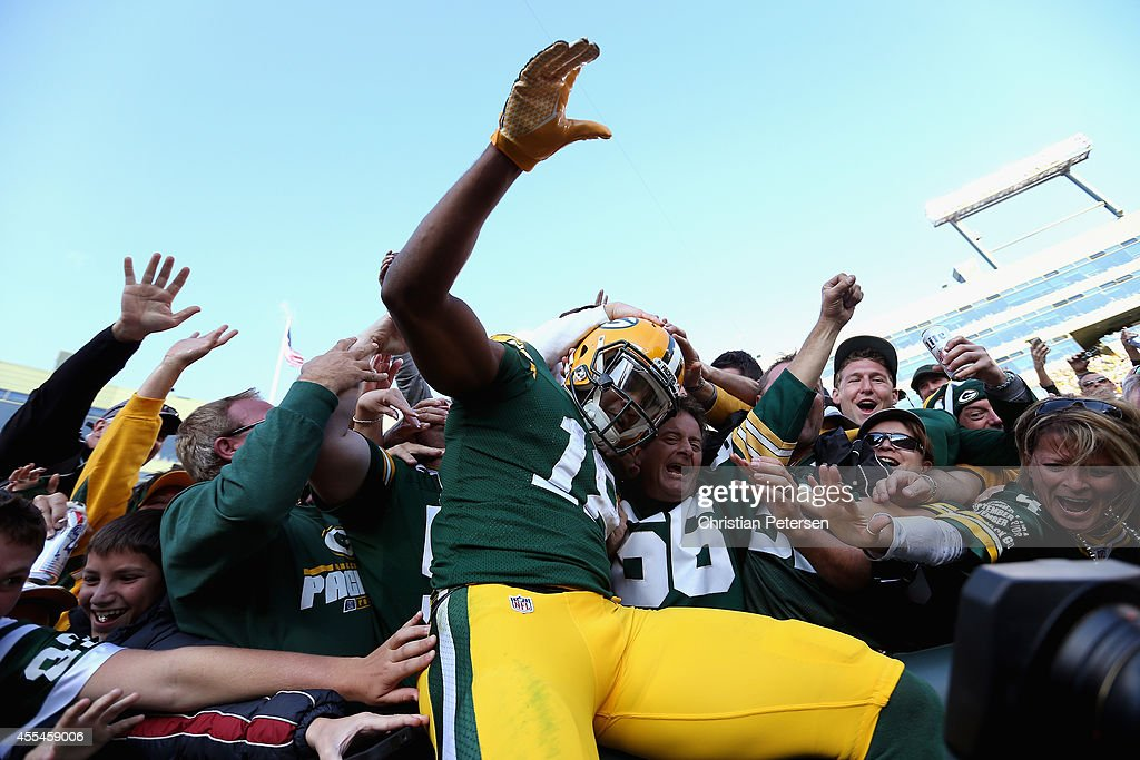 Wide receiver Randall Cobb #18 of the Green Bay Packers leaps into the crowd after scoring a touchdown against the New York Jets in the third quarter during the NFL game at Lambeau Field on September 14, 2014 in Green Bay, Wisconsin.