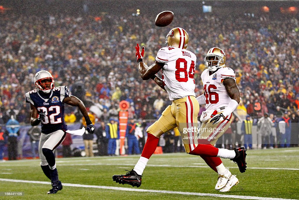 Wide receiver <a gi-track='captionPersonalityLinkClicked' href=/galleries/search?phrase=Randy+Moss&family=editorial&specificpeople=201999 ng-click='$event.stopPropagation()'>Randy Moss</a> #84 of the San Francisco 49ers catches a pass thrown by quarterback Colin Kaepernick #7 to score a touchdown in the first quarter against free safety <a gi-track='captionPersonalityLinkClicked' href=/galleries/search?phrase=Devin+McCourty&family=editorial&specificpeople=4510365 ng-click='$event.stopPropagation()'>Devin McCourty</a> #32 of the New England Patriots at Gillette Stadium on December 16, 2012 in Foxboro, Massachusetts.