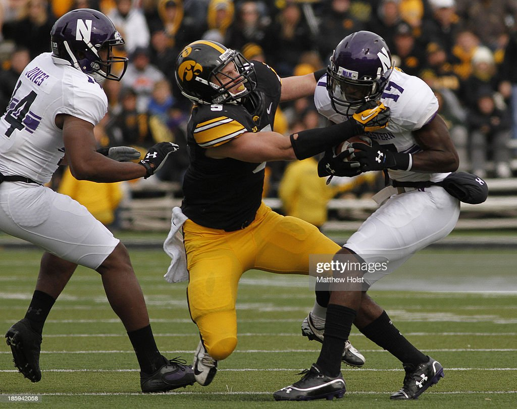 Wide receiver Rashad Lawrence #17 of the Northwestern Wildcats spins out of a tackle by defensive back Tanner Miller #5 of the Iowa Hawkeyes during the second quarter on October 26, 2013 at Kinnick Stadium in Iowa City, Iowa.