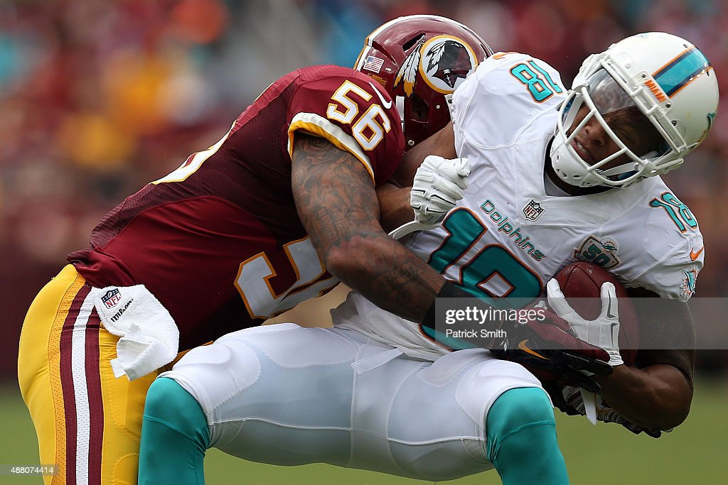 Wide receiver Rishard Matthews of the Miami Dolphins is tackled by inside linebacker Perry Riley of the Washington Redskins in the second half during...