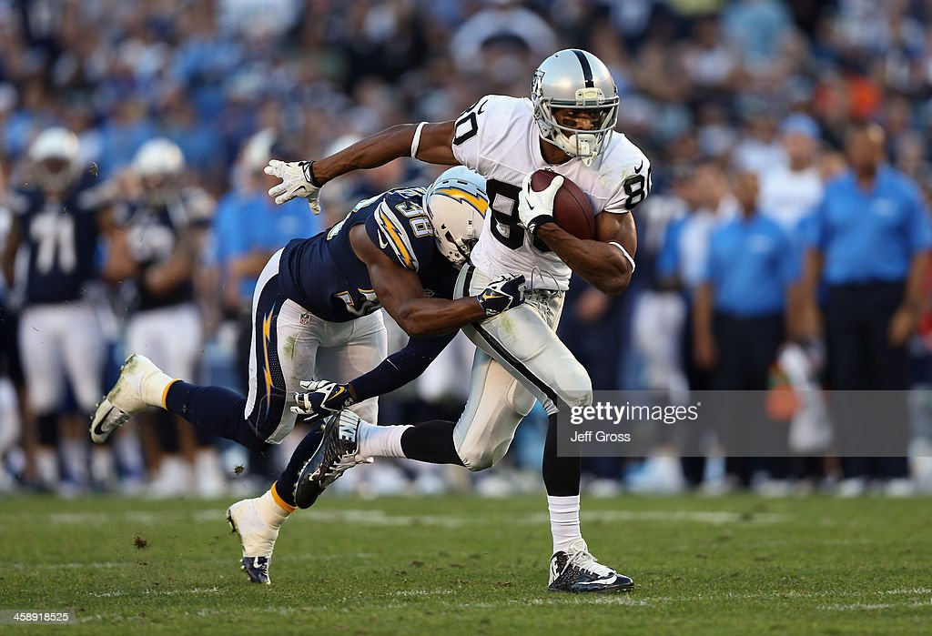 Wide receiver Rod Streater #80 of the Oakland Raiders is brought down by strong safety Marcus Gilchrist #38 of the San Diego Chargers in the second half at Qualcomm Stadium on December 22, 2013 in San Diego, California. The Chargers defeated the Raiders 26-13.