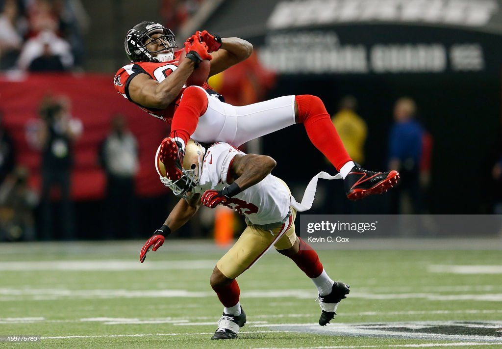 Wide receiver Roddy White #84 of the Atlanta Falcons catches a pass as he is hit by free safety Dashon Goldson #38 of the San Francisco 49ers in the first quarter in the NFC Championship game at the Georgia Dome on January 20, 2013 in Atlanta, Georgia.