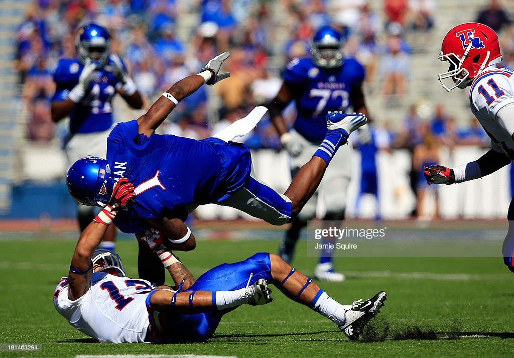 Wide receiver Rodriguez Coleman #1 of the Kansas Jayhawks is upended by defensive back Le'Vander Liggins #13 of the Louisiana Tech Bulldogs during the game at Memorial Stadium on September 21, 2013 in Lawrence, Kansas.