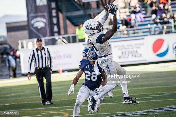 Wide receiver Ron'Quavion Tarver of the Utah State Aggies catches the ball as Elijah Mitchell of the Nevada Wolf Pack looks on at Mackay Stadium on...