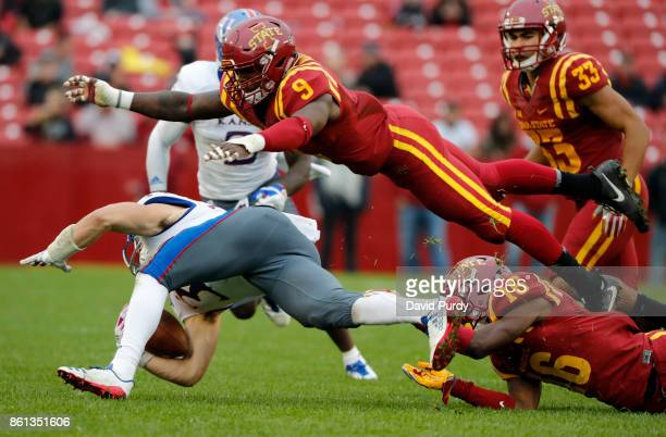 Wide receiver Ryan Schadler of the Kansas Jayhawks is tackled by linebacker Reggan Northrup and defensive back Keontae Jones of the Iowa State...