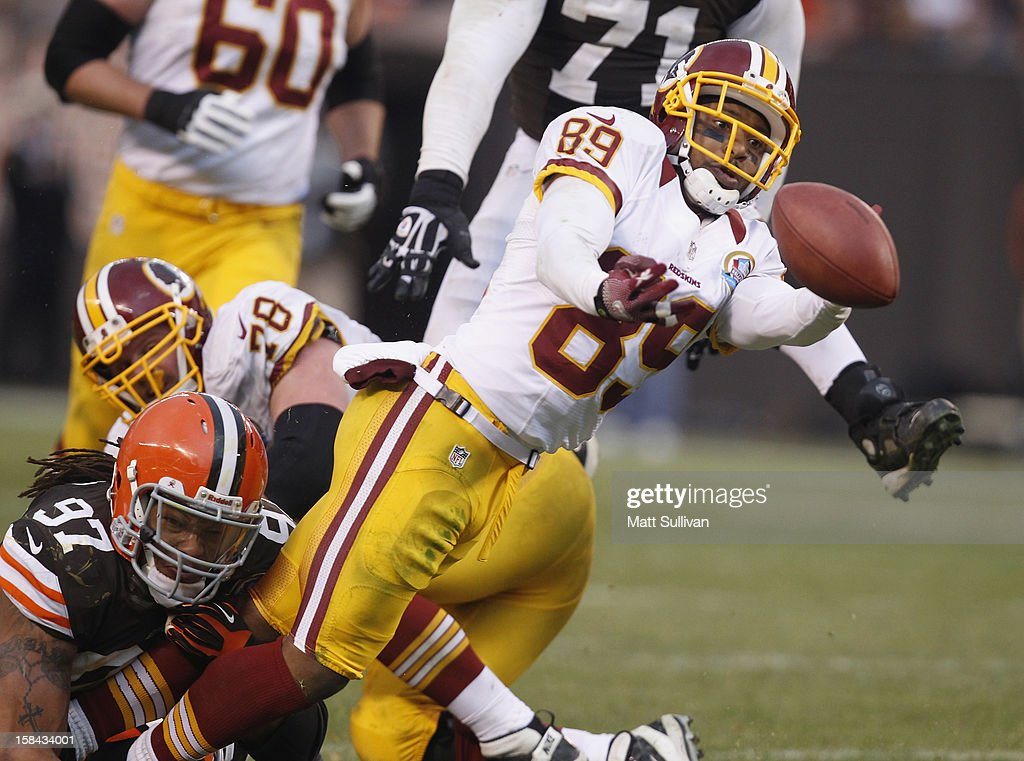 Wide receiver <a gi-track='captionPersonalityLinkClicked' href=/galleries/search?phrase=Santana+Moss&family=editorial&specificpeople=204490 ng-click='$event.stopPropagation()'>Santana Moss</a> #89 of the Washington Redskins fumbles the ball as he is hit by defensive lineman Jabaal Sheard #97 of the Cleveland Browns at Cleveland Browns Stadium on December 16, 2012 in Cleveland, Ohio.