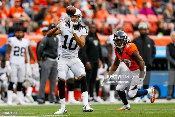 Wide receiver Seth Roberts of the Oakland Raiders has a catch under coverage by free safety Bradley Roby of the Denver Broncos at Sports Authority...