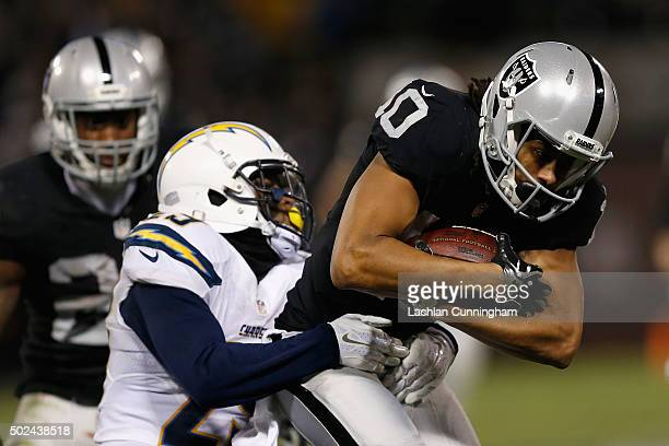 Wide receiver Seth Roberts of the Oakland Raiders is tackled by cornerback Craig Mager of the San Diego Chargers in overtime at Oco Coliseum on...
