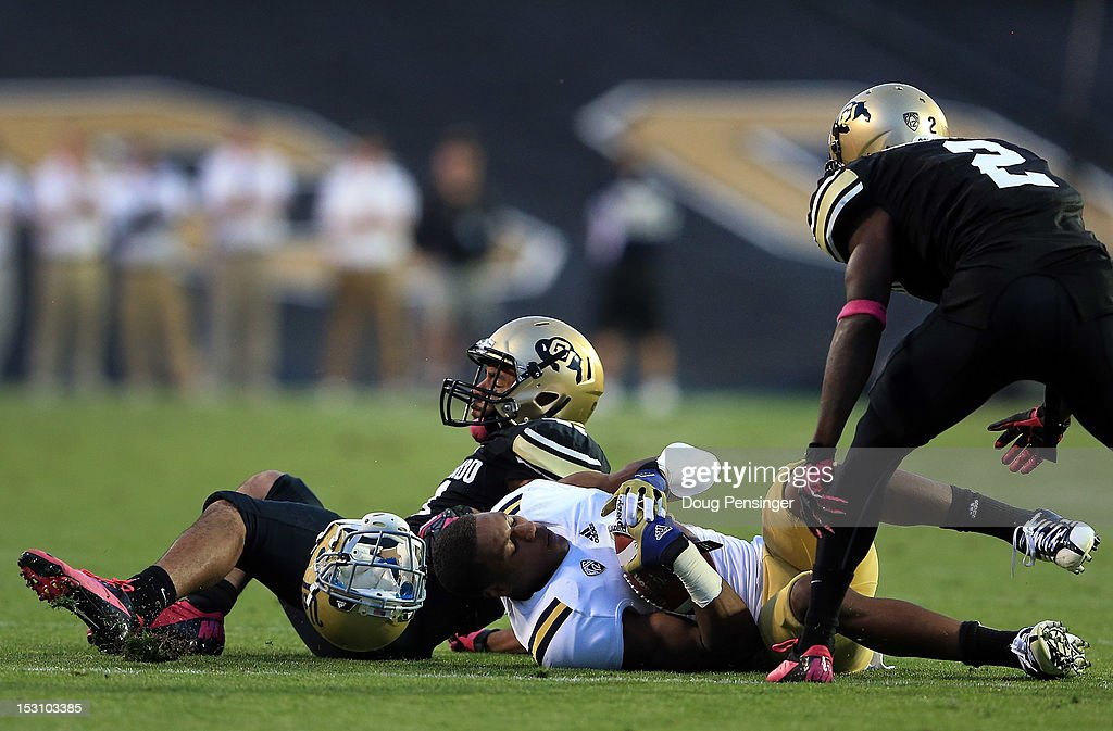 Wide receiver Shaquelle Evans #1 of the UCLA Bruins looses his helmet as he tackled by defensive back Terrel Smith #41 of the Colorado Buffaloes at Folsom Field on September 29, 2012 in Boulder, Colorado. UCLA defeated Colorado 42-14.