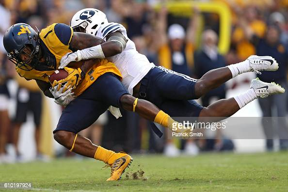 Wide receiver Shelton Gibson of the West Virginia Mountaineers is tackled by defensive back Dayan Lake of the Brigham Young Cougars during the second...