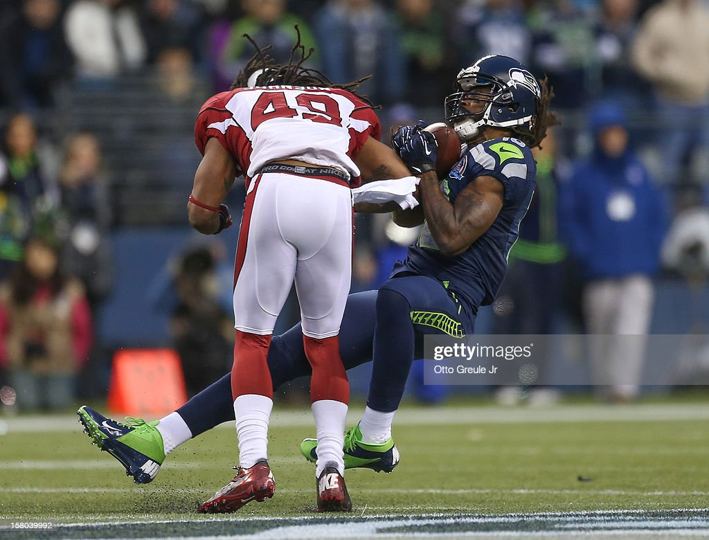 Wide receiver <a gi-track='captionPersonalityLinkClicked' href=/galleries/search?phrase=Sidney+Rice&family=editorial&specificpeople=793737 ng-click='$event.stopPropagation()'>Sidney Rice</a> #18 of the Seattle Seahawks is tackled after an 18 yard gain by strong safety <a gi-track='captionPersonalityLinkClicked' href=/galleries/search?phrase=Rashad+Johnson&family=editorial&specificpeople=3941326 ng-click='$event.stopPropagation()'>Rashad Johnson</a> #49 of the Arizona Cardinals at CenturyLink Field on December 9, 2012 in Seattle, Washington. Johnson was penalized for unnecessary roughness and the Seahawks went on to defeat the Cardinals 58-0.