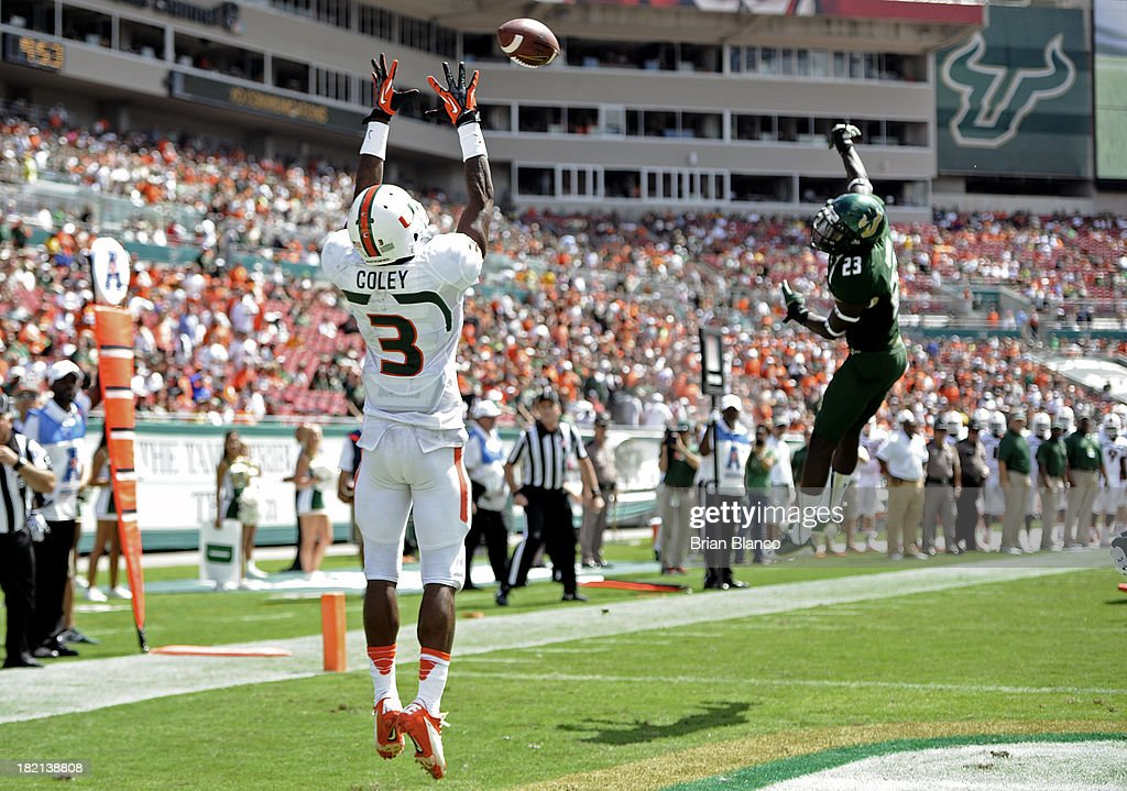Wide receiver Stacy Coley #3 of the Miami Hurricanes hauls in an 11-yard touchdown pass in front of Defensive back Kenneth Durden #23 of the South Florida Bulls during the third quarter on September 28, 2013 at Raymond James Stadium in Tampa, Florida.