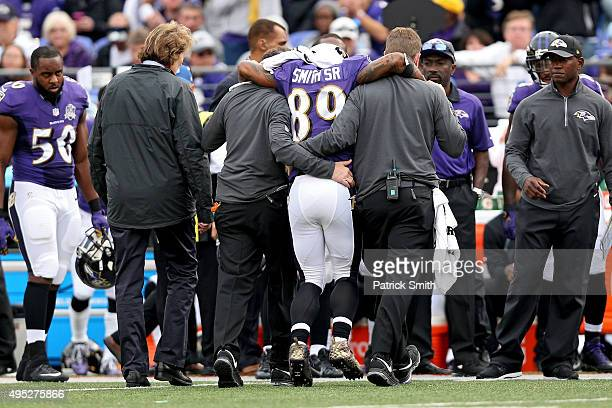 Wide receiver Steve Smith of the Baltimore Ravens is helped off the field by medial staff after being injured in the third quarter against the San...