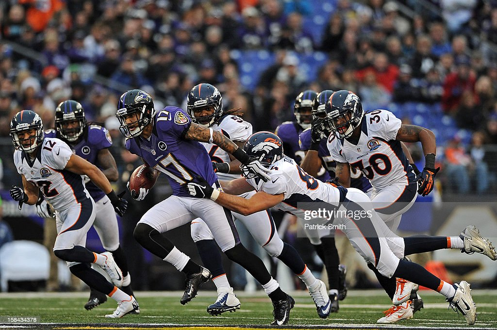 Wide receiver Tandon Doss #17 of the Baltimore Ravens is pulled down by Jacob Tamme #84 of the Denver Broncos in the third quarter at M&T Bank Stadium on December 16, 2012 in Baltimore, Maryland. The Denver Broncos won, 34-17.