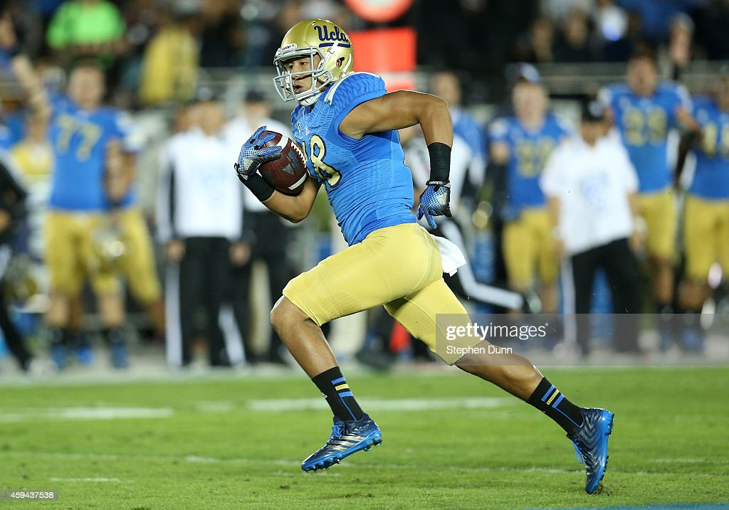Wide receiver Thomas Duarte #18 of the UCLA Bruins carries on his way to scoring on a 57 yard touchdown pass play against the USC Trojans in the first quarter at the Rose Bowl on November 22, 2014 in Pasadena, California.